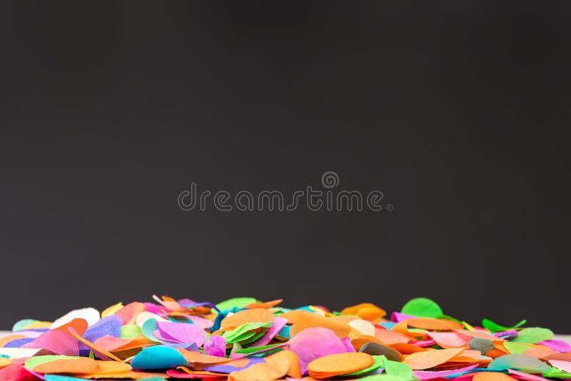 在黑色页岩的五颜六色的五彩纸屑作为庆祝的模板 库存图片