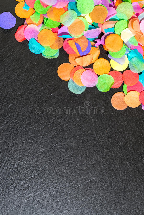 在黑色页岩的五颜六色的五彩纸屑作为庆祝的模板 库存照片