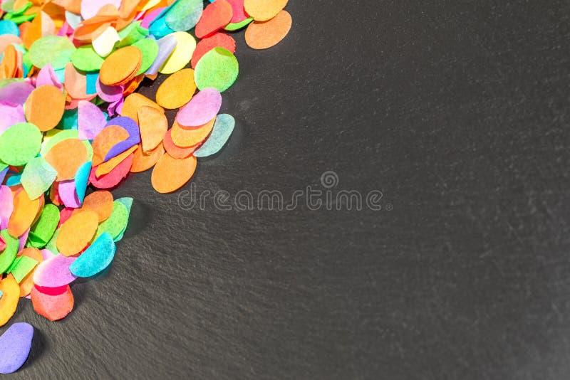在黑色页岩的五颜六色的五彩纸屑作为庆祝的模板 免版税库存图片