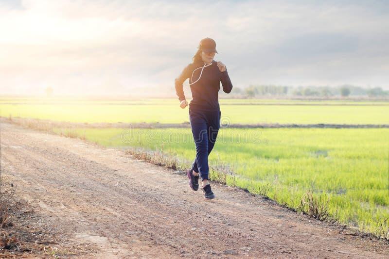 在绿色领域日落后面农村路的妇女连续锻炼  免版税库存图片