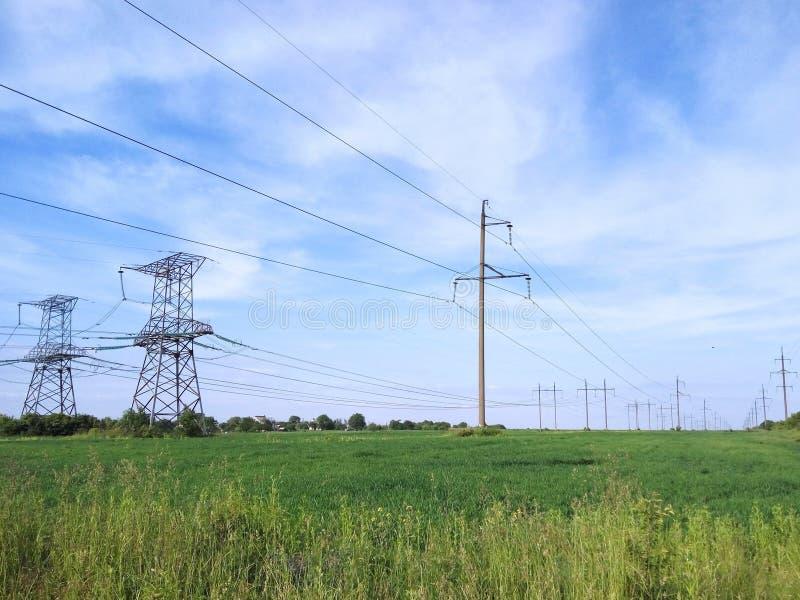 在绿色领域的电定向塔 免版税库存图片