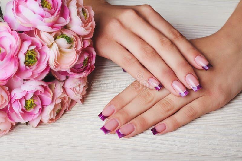 在紫色颜色的法国钉子艺术 库存照片