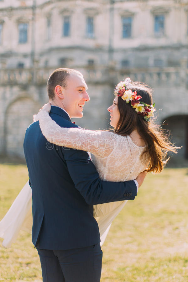 在绿色晴朗的草坪的有吸引力的新婚佳偶对在美丽的被破坏的巴洛克式的宫殿附近 拿着迷人的新娘的爱恋的新郎 库存图片
