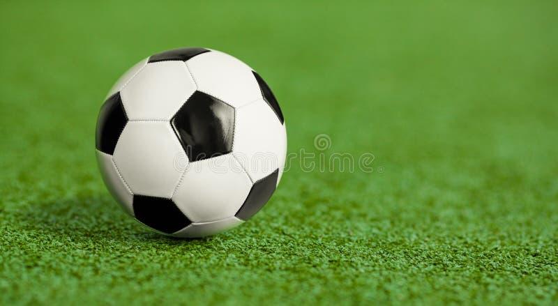 在绿草操场的足球 免版税图库摄影
