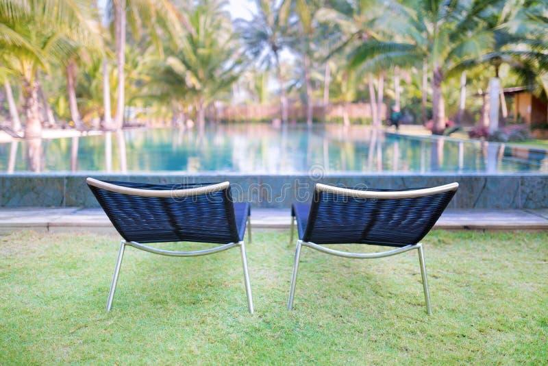 在绿草的两张舒适的躺椅在swimmi附近 库存图片