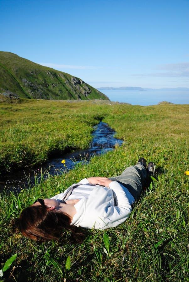 在绿草的妇女说谎的仰近的小河 免版税库存照片