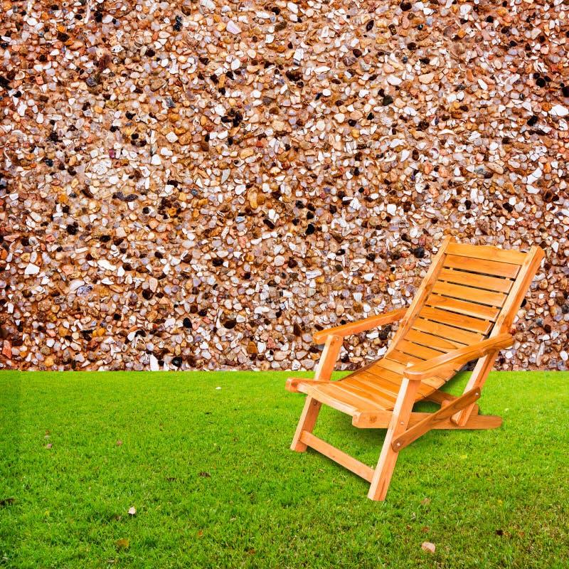 在绿草的木轻便折叠躺椅与石墙 免版税库存照片