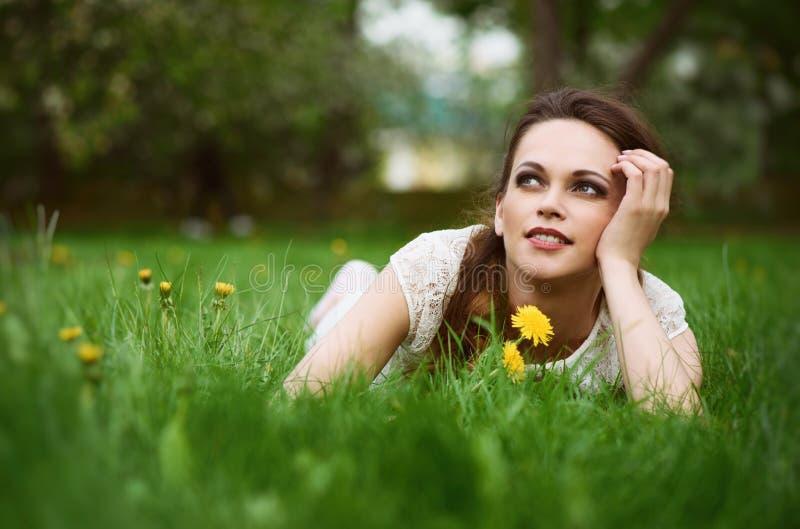 在绿草的美丽的少妇 免版税库存照片