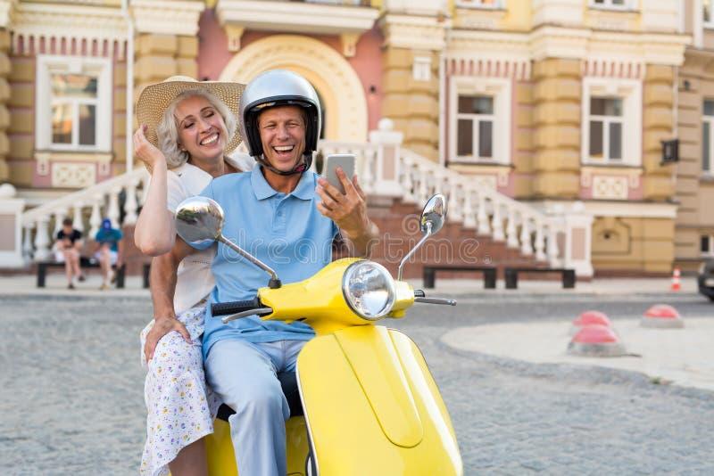 在滑行车的夫妇有电话的 免版税库存照片