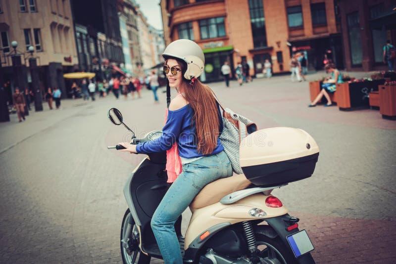 在滑行车附近的年轻快乐的女孩在欧洲城市 图库摄影