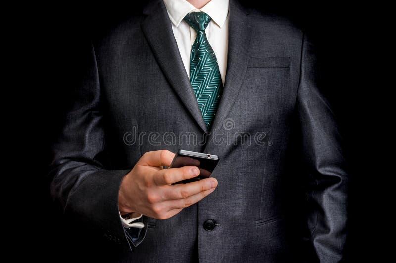 在黑衣服的商人与手机 库存照片