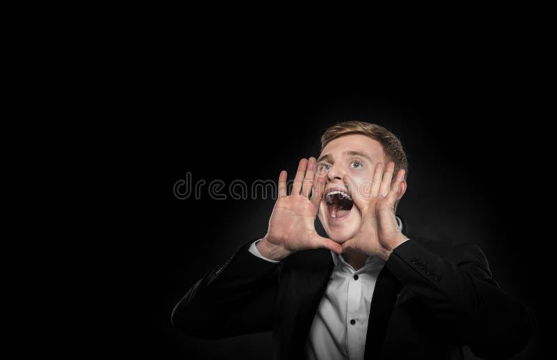 在黑衣服的商人呼喊提起他的手 库存图片
