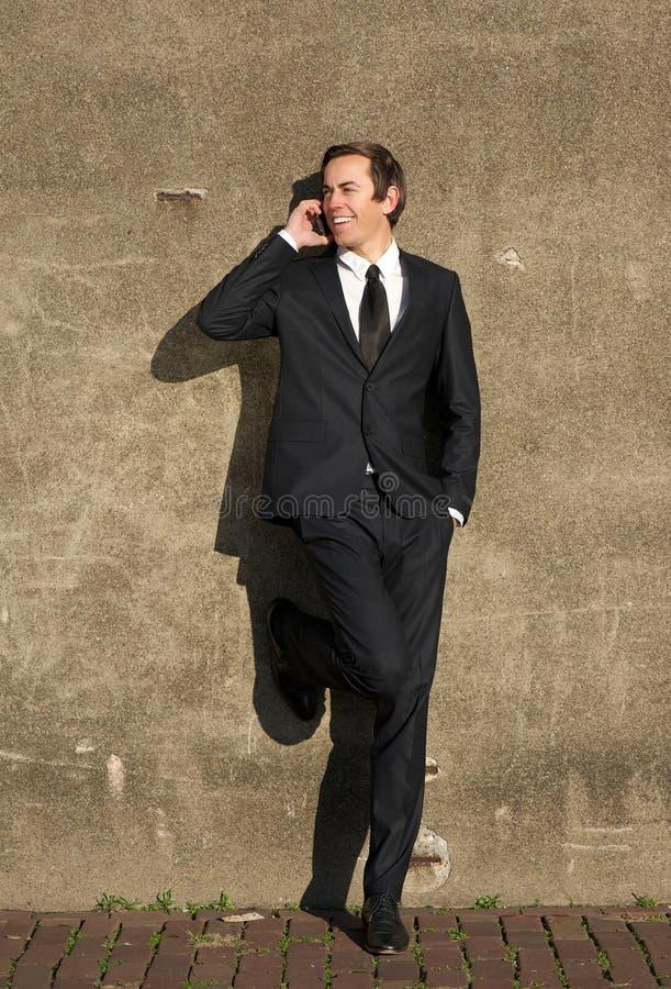 在黑衣服的商人谈话在手机户外 库存图片