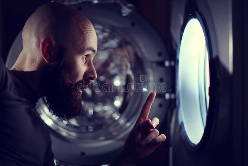 在洗衣机旁边的人 免版税库存照片