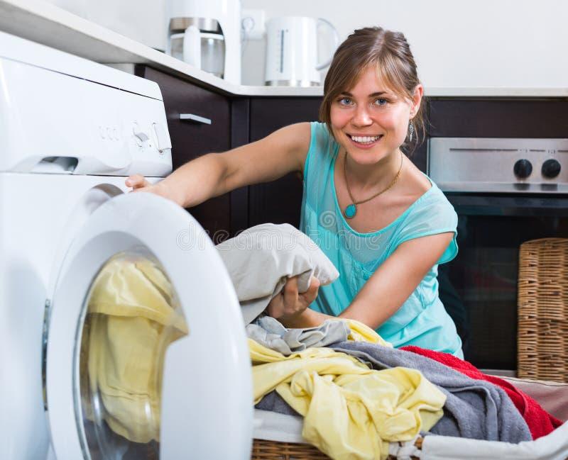 在洗衣机附近的主妇 免版税库存图片