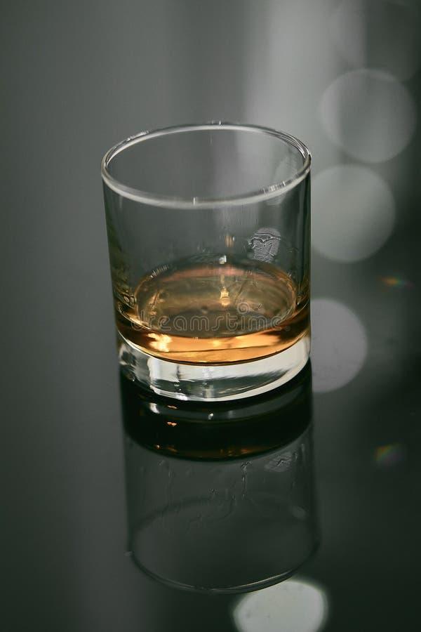 在黑表上的平直的威士忌酒玻璃与反射 库存图片