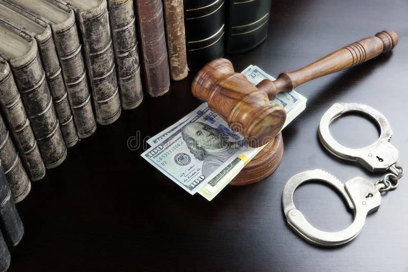 在黑表上的法官惊堂木、手铐、美元现金和书 免版税库存照片