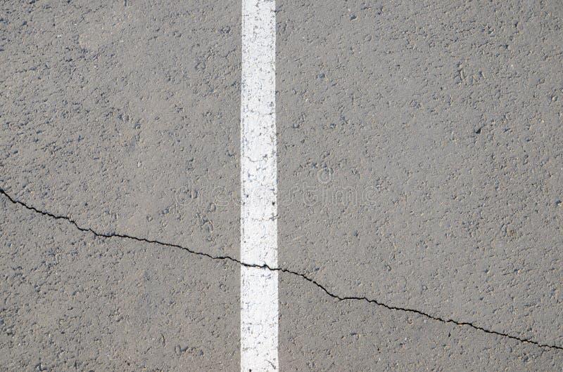 在破裂的沥青的白色条纹 免版税库存照片