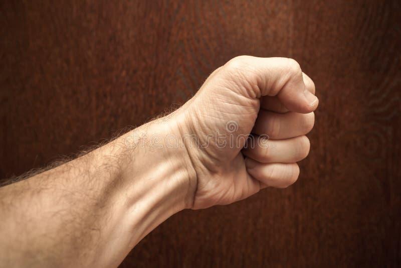 在黑褐色木墙壁的男性拳头 库存照片