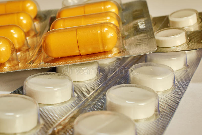 在说谎在一张白色桌上的包裹的药片 免版税库存照片
