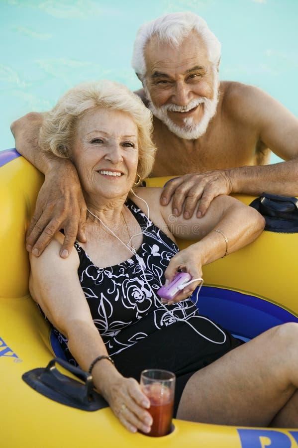 在说谎在可膨胀的木筏藏品的游泳池妇女的资深夫妇喝听便携式音乐播放画象。 库存照片