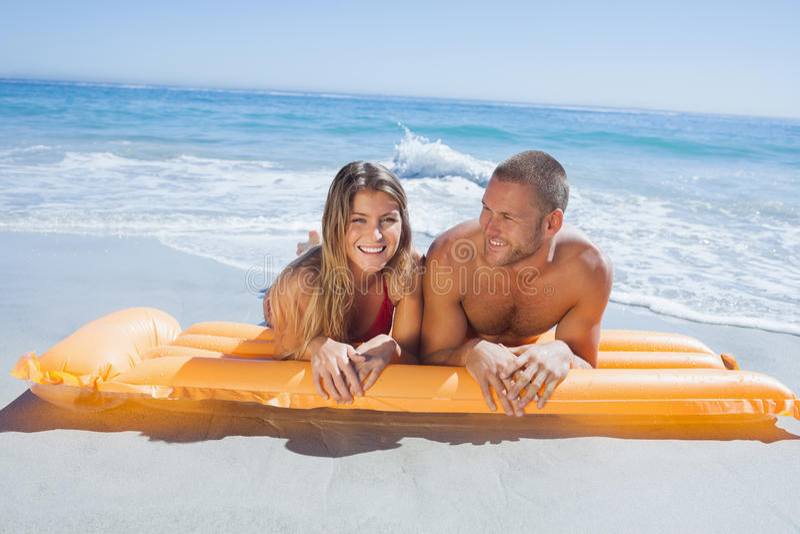 在说谎在海滩的泳装的快乐的逗人喜爱的夫妇 免版税库存照片
