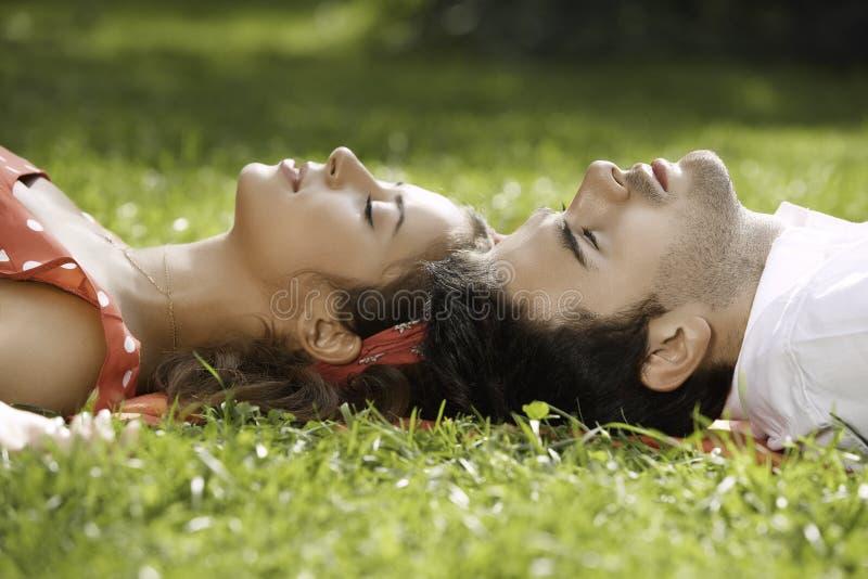 在说谎在草的爱的夫妇在公园 库存照片