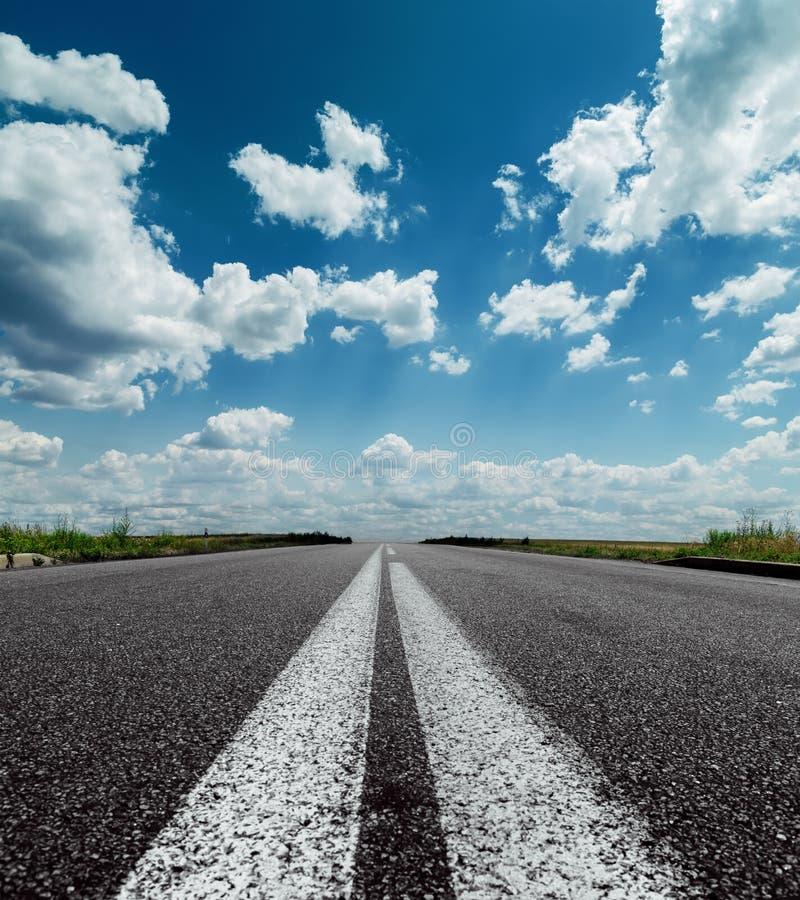 在黑路和剧烈的天空的两条空白线路 免版税图库摄影