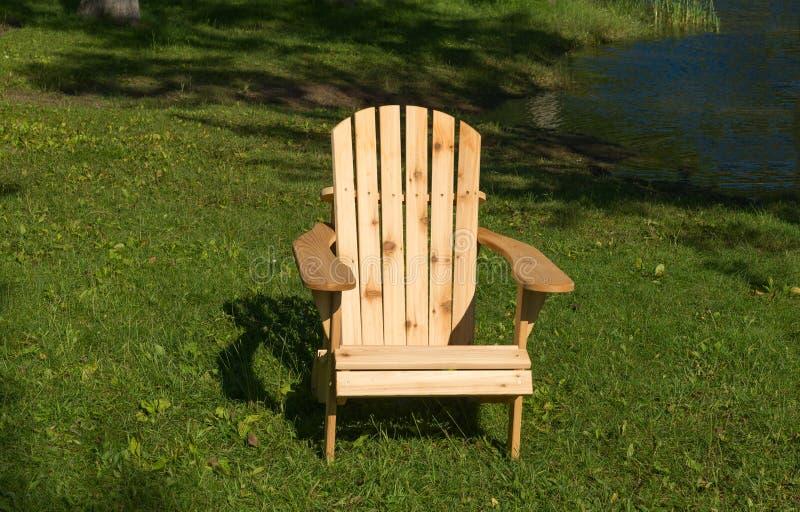 在水边缘的木椅子 免版税库存图片
