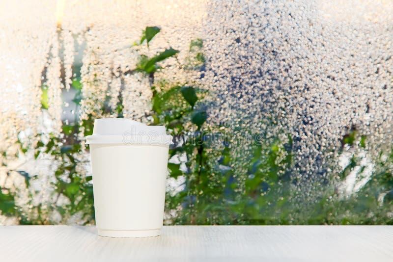 在临近雨天窗口背景的桌上的白色一次性咖啡杯 免版税库存图片