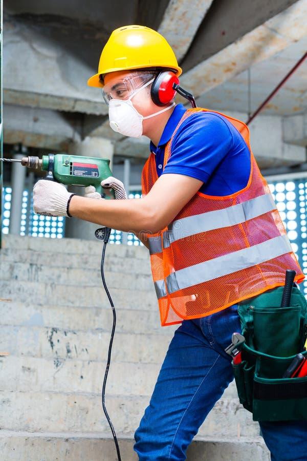 在建造场所墙壁的亚洲工作者钻井 免版税库存图片