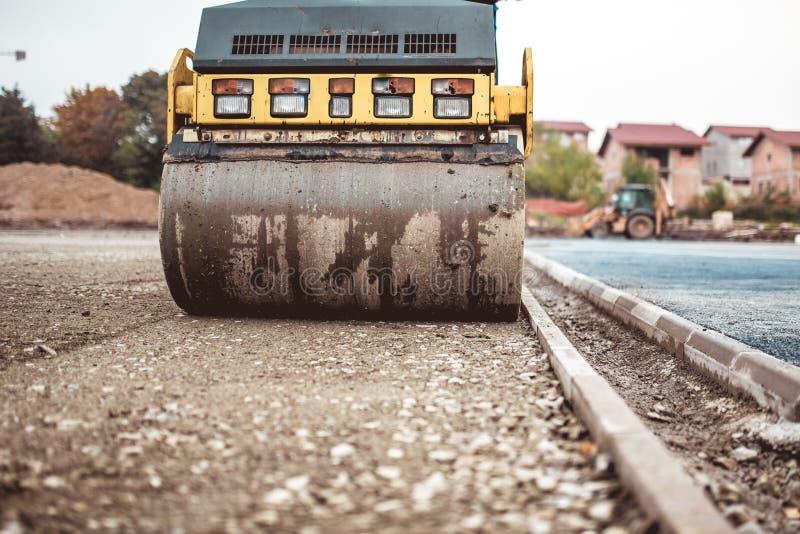 在建造场所的压紧机 铺和变紧密在高速公路建筑时的路 库存照片