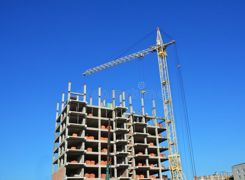 在建造场所的塔吊和大厦建设者 在建造场所的大厦起重机有建造者的 大厦高层 免版税库存图片