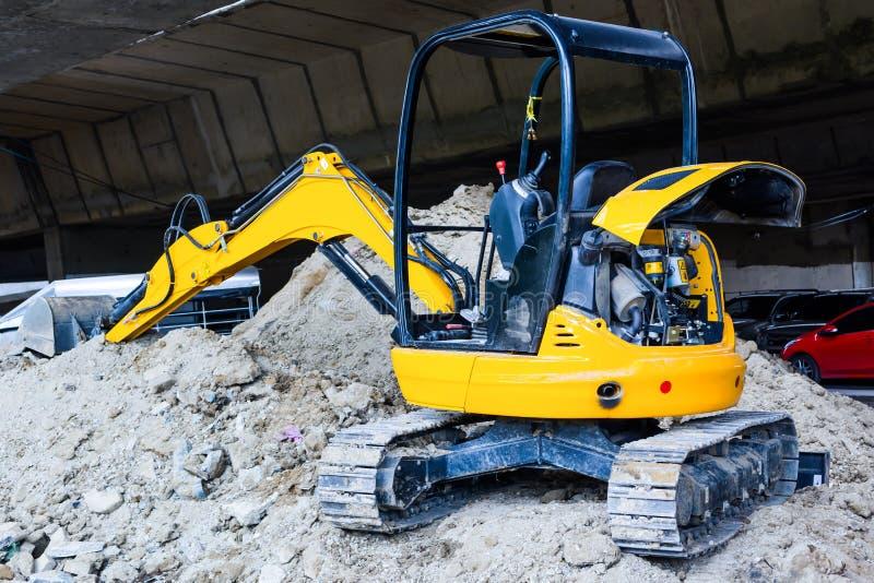 在建造场所的微型黄色挖掘机 免版税库存照片