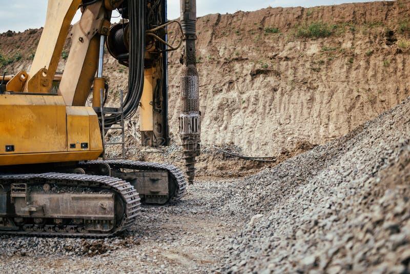 在建造场所的耐用机械 高速公路大厦细节与旋转钻探机器的 免版税库存照片
