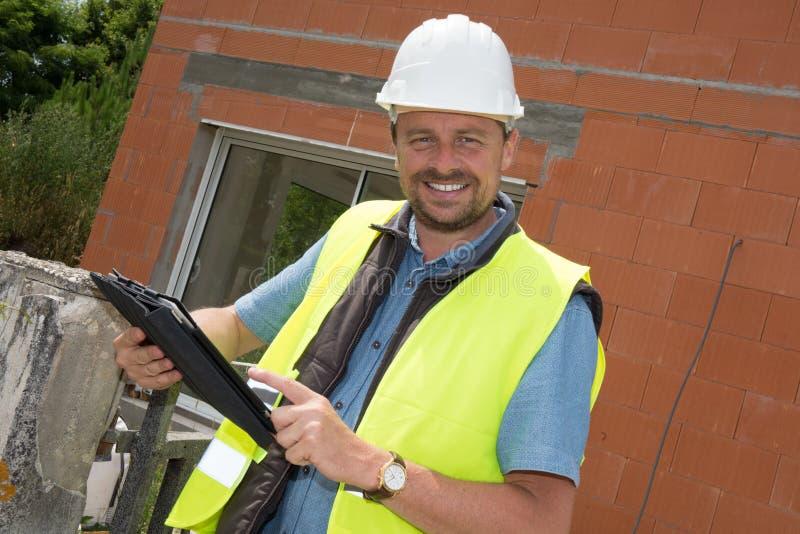 在建造场所的英俊的苦干者人画象 库存图片