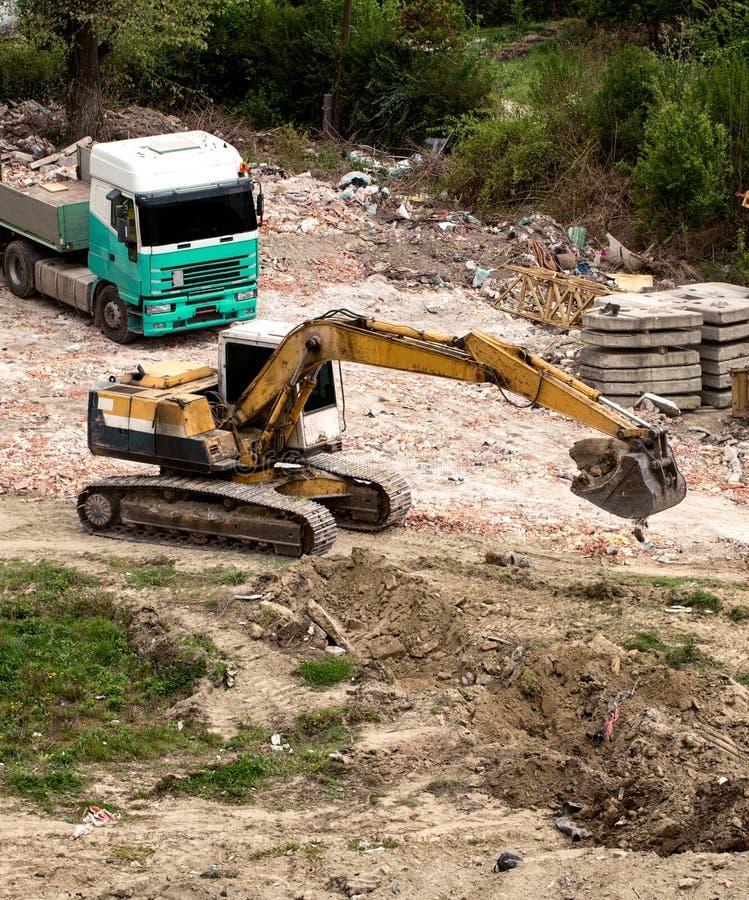 在建造场所的黄色履带牵引装置挖掘机机器 库存照片
