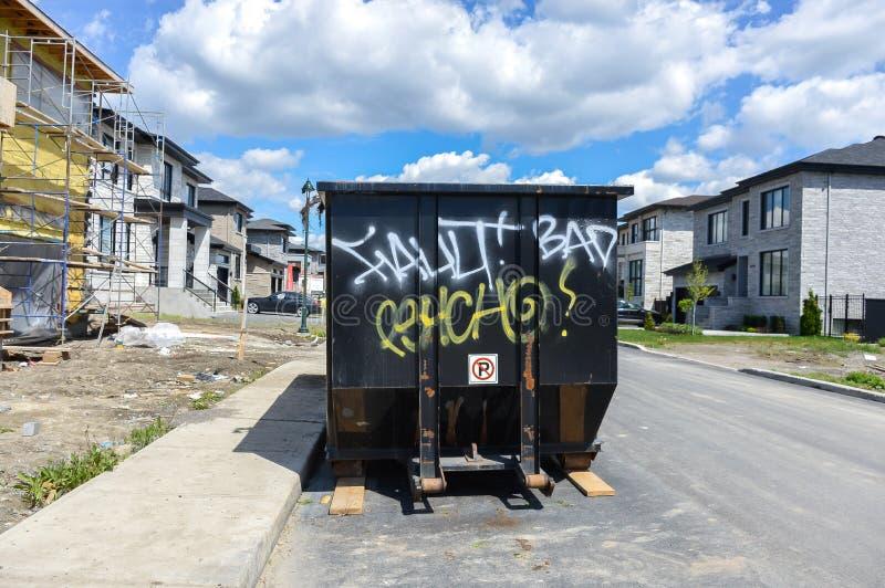 在建造场所附近的被装载的大型垃圾桶 图库摄影