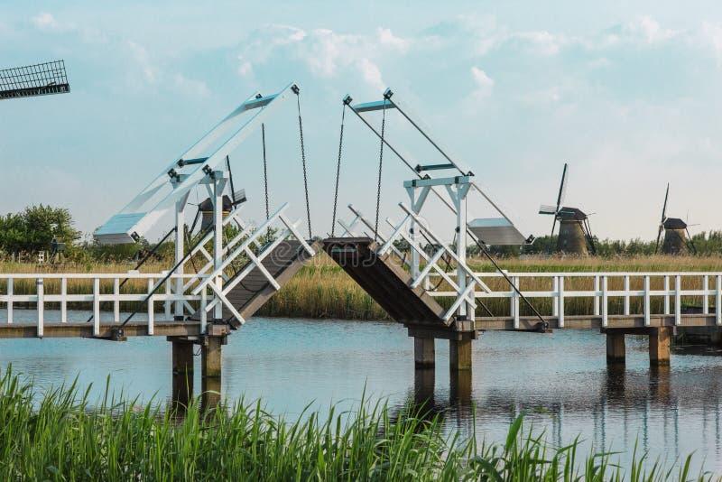 在水道附近的美丽的传统荷兰风车有吊桥的 免版税图库摄影