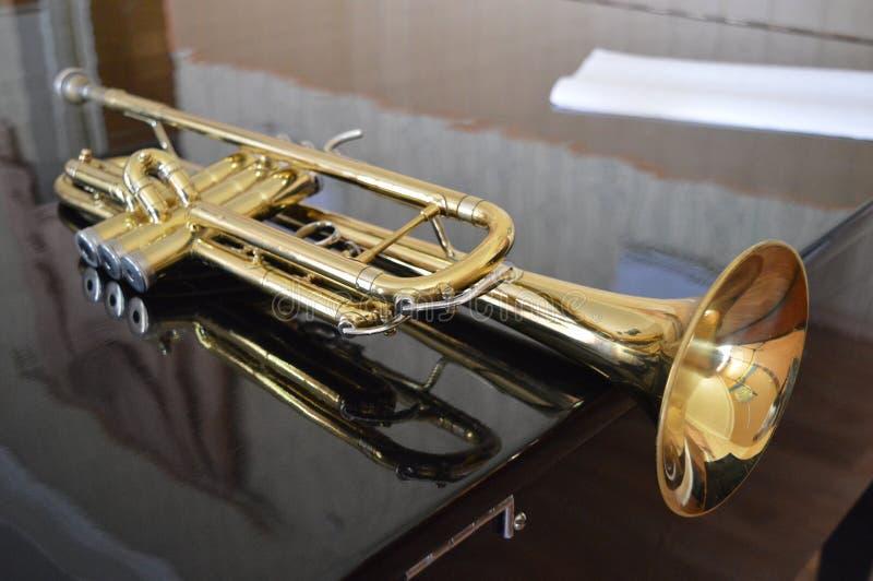 在黑钢琴的黄铜喇叭 库存图片