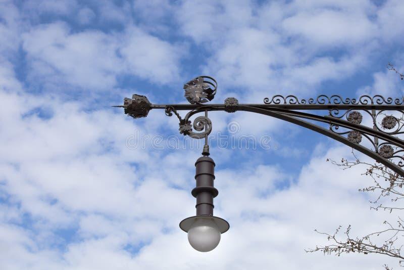 在锻铁的古色古香的街灯 覆盖天空 库存图片