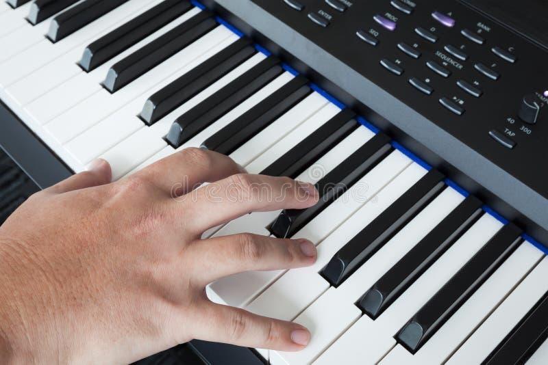 在琴键合成器特写镜头钥匙额骨视图的手 库存图片