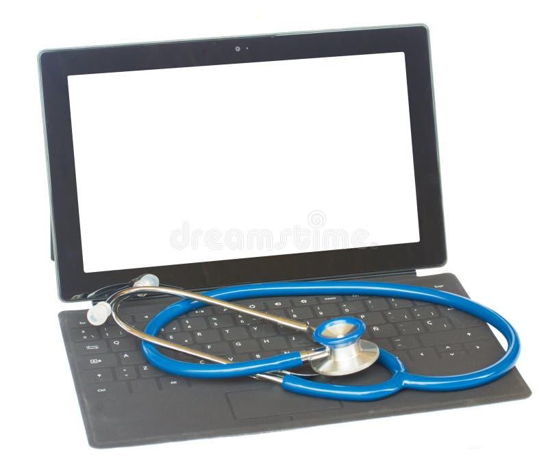 在黑键盘的听诊器 库存图片