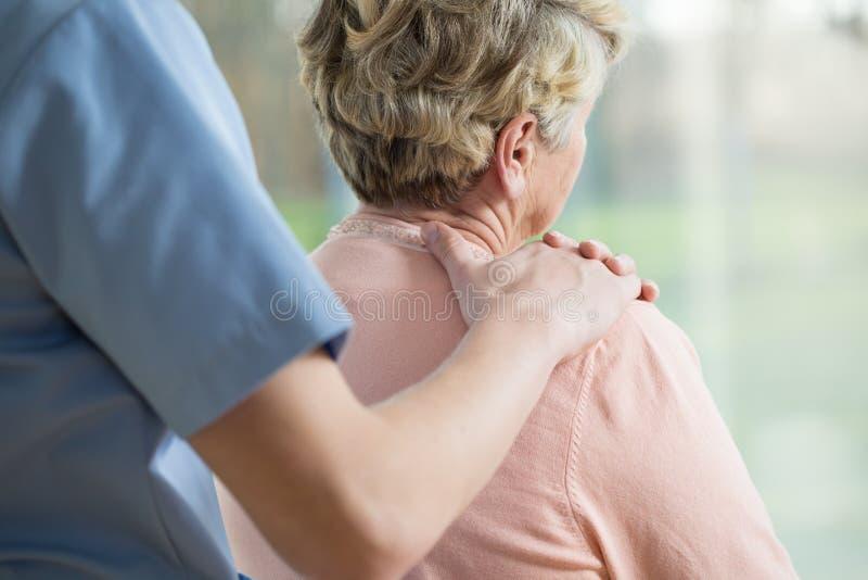 在年长妇女的肩膀的手 库存图片
