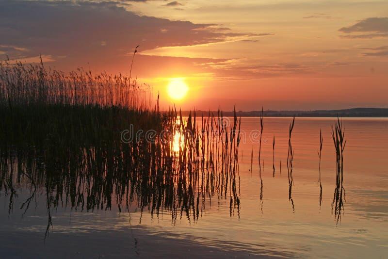 在水附近的安静的日落 免版税库存照片