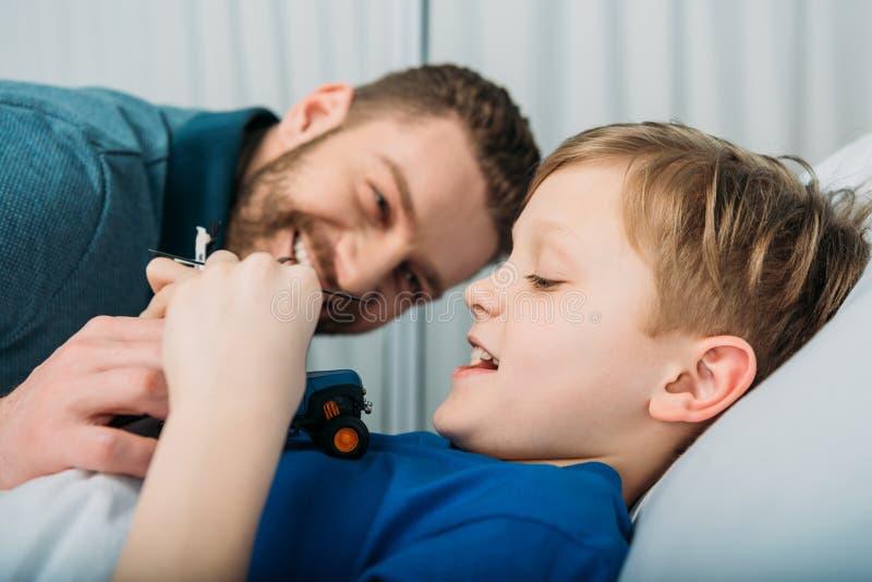 在医院生使用与在医院病床、爸爸和儿子上的病的小男孩 图库摄影