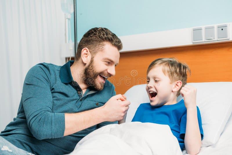 在医院生使用与在医院病床、爸爸和儿子上的逗人喜爱的矮小的儿子 库存照片