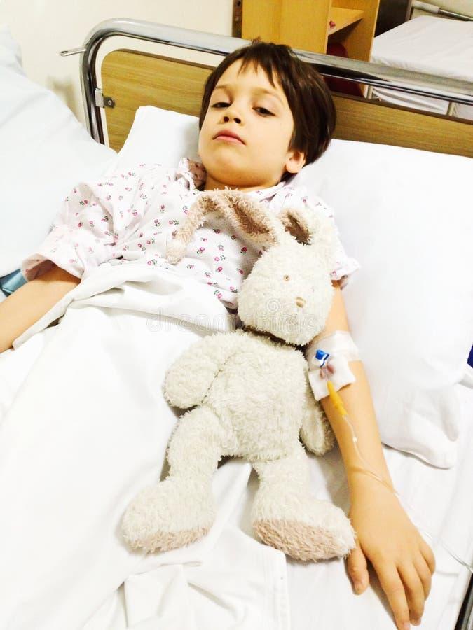 在医院病床上的哀伤的孩子 免版税图库摄影