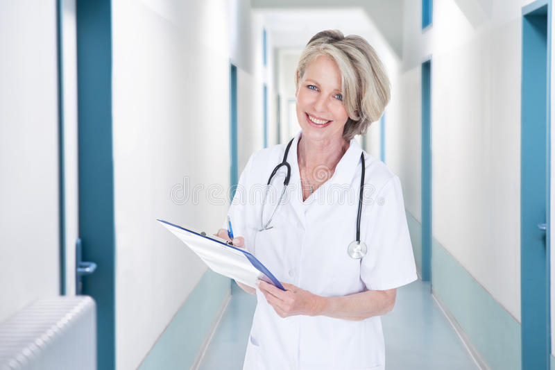 在医院走廊的女性医生文字笔记 库存照片