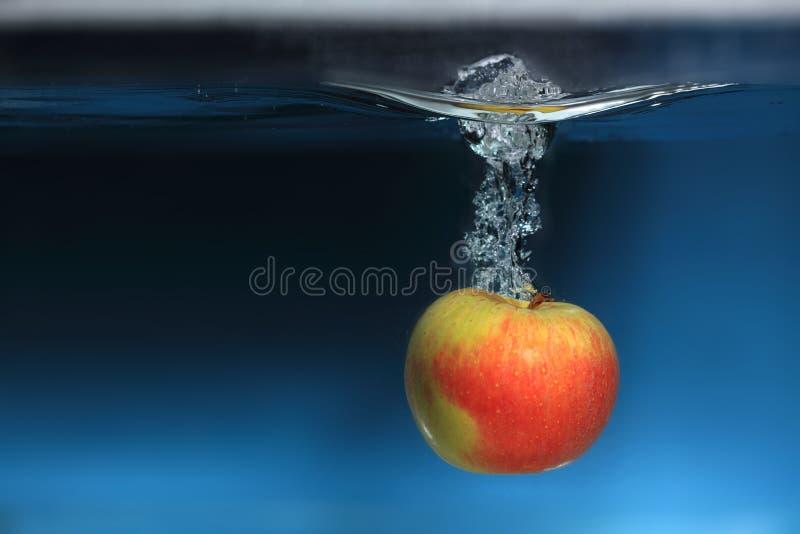 在水飞溅的苹果计算机在蓝色背景 免版税库存图片